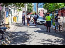 Police maintain a strong presence in Allman Town, Kingston, after Sunday's murder of three men on Prince of Wales Street.