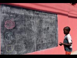 Eight-year-old Ajanie Stephenson from Tavares Gardens in St Andrew and a student at the Cockburn Gardens Primary and Junior High School, looks at school work placed on a wall located in the community on Tuesday.