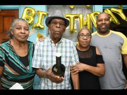 Adolphus Powell (second left) celebrates his 100th birthday with his children (from left) Audrey, Andrea and Desmond, at his home.