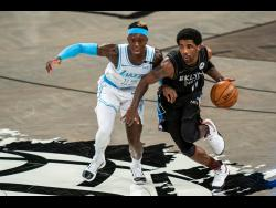 Los Angeles Lakers guard Dennis Schroeder (left) defends against Brooklyn Nets guard Kyrie Irving during the first half of an NBA basketball game on Saturday, April 10, in New York.