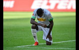 Moenchengladbach's Marcus Thuram taking the knee after scoring his side's second goal during the German Bundesliga soccer match against Union Berlin in Moenchengladbach, Germany, on Sunday, May 31.