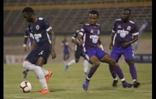 File Photos Nickache Murray of Jamaica College (left) moves away from Kingston College defenders during their ISSA Champions Cup semi-final game at the National Stadium on Saturday, November 16, 2019.