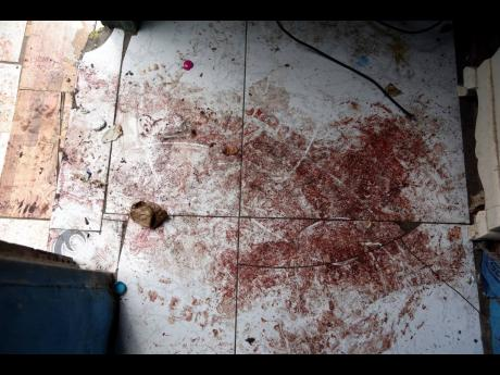 The bloodstained floor of the Penn Street dwelling where Jenell Thomas and her brother Omar Jarrett were killed Monday night.