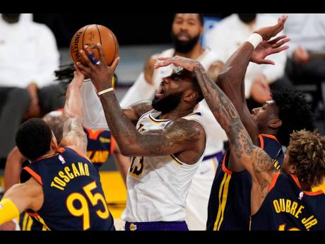 Los Angeles Lakers forward LeBron James (second from left) is fouled by Golden State Warriors guard Kelly Oubre Jr (right) while shooting as forward Juan Toscano-Anderson (left) and guard Jordan Poole defend during the first half of an NBA basketball game on Sunday, February 28, 2021.